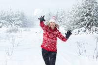 Playful woman throwing a snowball