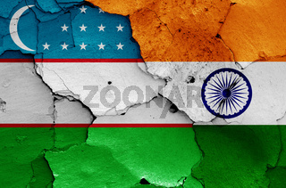 flags of Uzbekistan and India painted on cracked wall