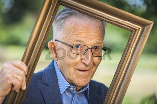 Mischievous look of a pensioner through picture frames