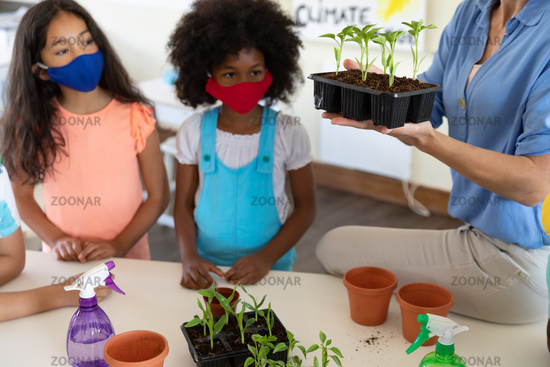 Mid section of female teacher wearing face mask showing plant pots to students in class