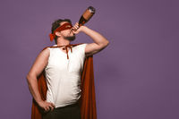 Super antihero man drinks alcohol from the throat of a bottle. Isolated on grape purple background with copy space or textspace at right side