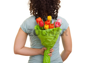 Young natural woman with curly hair holding a bouquet of colorful tulips behind her back, isolated on white background. Mothers day, Valentines day, Easter and surprise Concept.