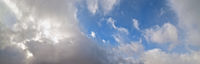 Blue sky with clouds in sunlight, wide cloudscape background panorama