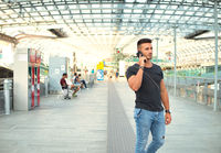 Attractive young man in train station using cellphone