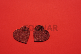 two glitter hearts on red background