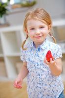 Kind hält frische Erdbeere in der Hand