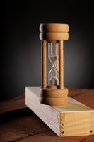 Antique HourGlass Time on wood block with dark background