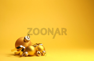 Three golden vintage Christmas baubles on a yellow background