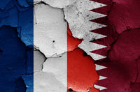 flags of France and Qatar painted on cracked wall
