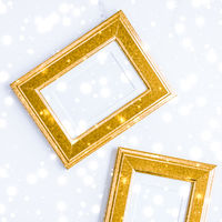 Golden photo frame and glowing glitter snow on marble flatlay background for Christmas and winter holidays