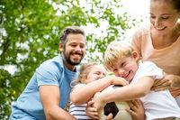 Familie und Kinder streiten um Fußball im Garten