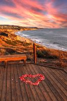 Sunset over Crystal Cove State Park Beach and a heart of rose petals on a wooden boardwalk that overlooks the coastline of Southern California on Valentine's Day.