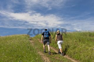 Junges Paar wandert auf einem Feldweg über eine Sommerwiese unter blauem Himmel im Kaiserstuhl Gebirge