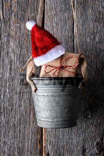 A plain paper wrapped Christams present with Santa hat in a small pail hanging on a rustic wood wall.