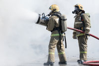 Two firefighters extinguish fire from fire hose, using firefighting water-foam barrel with air-mechanical foam