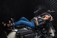 Cute woman lying on a motorcycle
