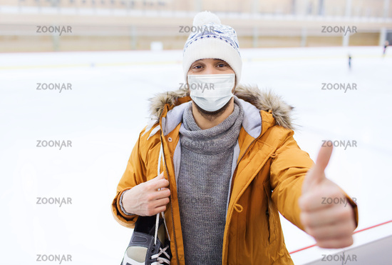 man in mask showing thumbs up on skating rink