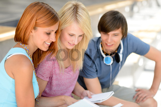 Three college friends studying looking into book