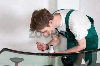 Worker in glazier's workshop preparing sealing for windscreen