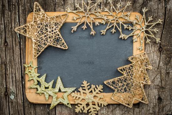 Gold Christmas tree decorations on vintage wooden blackboard