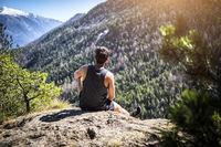 Young man sitting on a rock enjoying mountain view