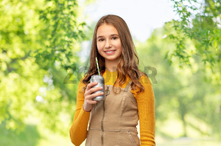happy teenage girl drinking soda from can