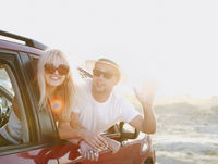Young stylish couple in sunglasses hugging near red car