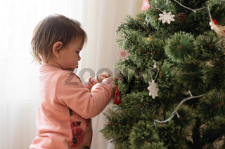 Toddler girl decorating christmas tree at home. December traditions for kids.