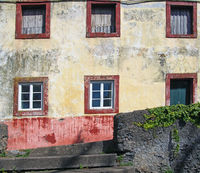 facade of a typical old spanish house painted in faded yellow and red colors surrounded by a grey wall with plants in Funchal, Tenerife