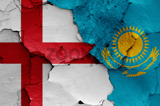 flags of England and Kazakhstan painted on cracked wall