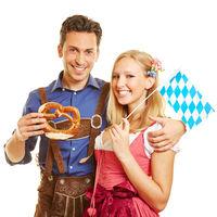 Bayrisches Paar mit Brezn und Fahne zum Oktoberfest