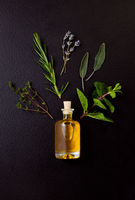 Bottle with organic essential oil from mint, lavender, sage, thyme, and rosemary