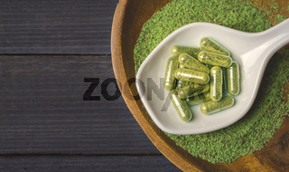 Top view of Kratom powder in wooden bowl and spoon and Kratom capsules