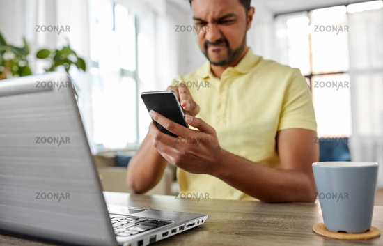 angry indian man with smartphone working at home