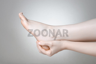 A young woman massaging her painful heel
