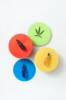 Colorful round cards with bottles of cannabis CBD oil on a light grey background.