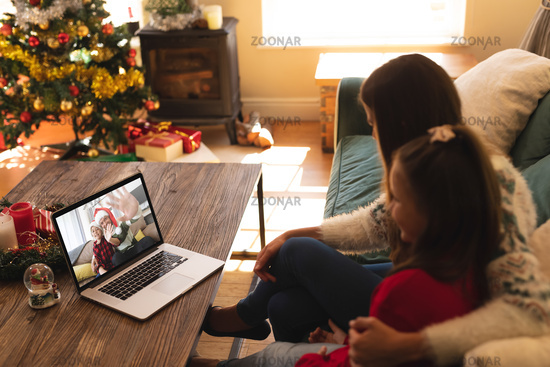 Woman and daughter sitting on couch having a videocall with man and son in santa hats waving on lapt