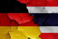 flags of Germany and Thailand painted on cracked wall