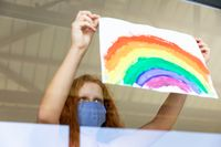 Girl wearing face mask sticking rainbow painting to the window
