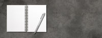 Blank open spiral notebook and pen isolated on dark concrete banner