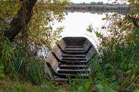 Holzboot zwischen Gras und Bäumen vor einem See im Gegenlicht