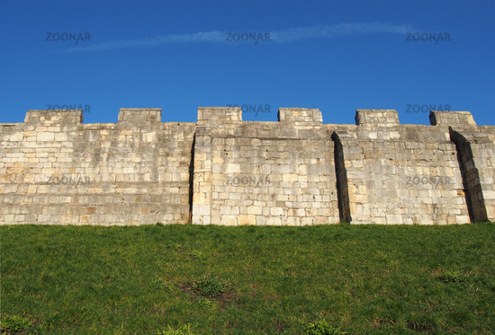 a view of the ancient medieval city walls of york with grass covered embankment and blue sky