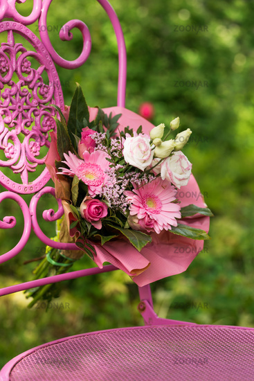Pink flower bouquet on a garden chair
