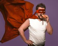 Hungry superhero man eats big hamburger with meat. Man in red flying cloak eats looking at camera on grape purple background. Fast food snack concept