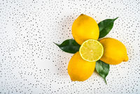 three lemons and a half with green leaves are dotted on a white surface.