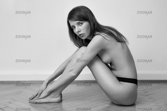 Topless young woman posing in her panties