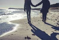 Mutter und Tochter spazieren am Strand
