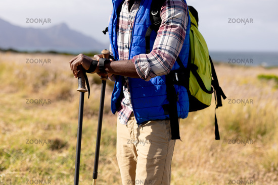 Fit african american man wearing backpack nordic walking on coast