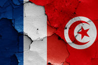 flags of France and Tunisia painted on cracked wall