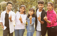 Group of teenager friends showing ink marked fingers outside polling station or booth after casting votes - Concept of Indian election or vote casting system.